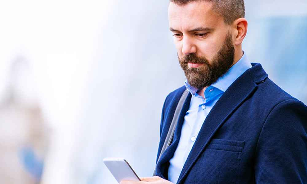 a man in a suit looking at his phone screen