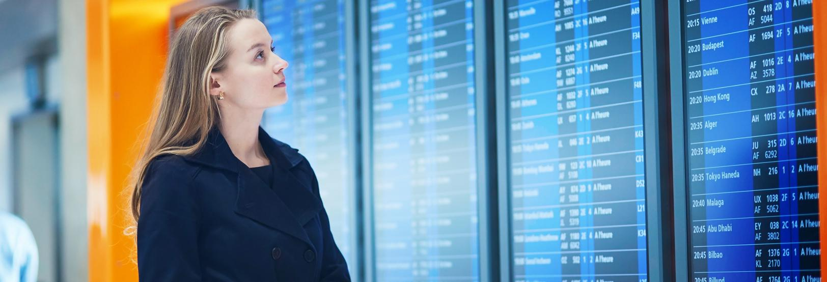 woman looking at transportation schedule screen